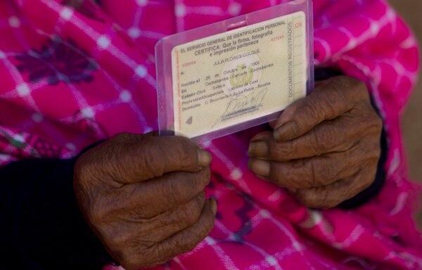 La indígena boliviana enseña su documento que cetifica su nacimiento, pero este tipo de documentos comenzaron a existir en Bolivia hasta 1940. Foto AP.