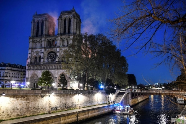 Firefighters work from a quay of the River Seine at the base of the Notre-Dame de Paris Cathedral during a fire that engulfed it roof on April 15, 2019, in the French capital Paris. - A huge fire swept through the roof of the famed Notre-Dame Cathedral in central Paris on April 15, 2019, sending flames and huge clouds of grey smoke billowing into the sky. The flames and smoke plumed from the spire and roof of the gothic cathedral, visited by millions of people a year. A spokesman for the cathedral told AFP that the wooden structure supporting the roof was being gutted by the blaze. (Photo by STEPHANE DE SAKUTIN / AFP)