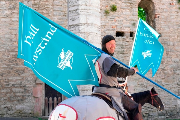 Thomas Lindgren on the horse Soprano, from the knight society Tornamenteum, carries flags reading