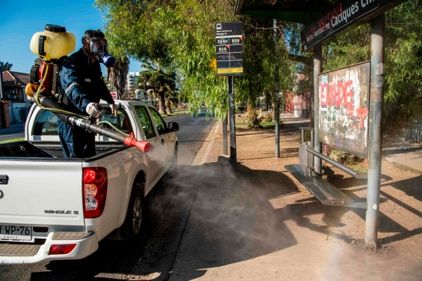 A worker disinfects a bus stop as a preventive measure against the spread of the new coronavirus, COVID-19, in Santiago, Chile, march 23,2020. - Chile declared a