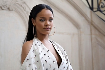 """FILE - In this Sept. 30, 2016, file photo, Singer Rihanna poses for photographers as she arrives to Christian Dior's Spring-Summer 2017 ready-to-wear fashion collection presented in Paris. Rihanna is mourning the death of her cousin and calling an end to gun violence. The singer posted three photos of herself with 21-year-old Tavon Kaiseen Alleyne on Instagram on Tuesday, Dec. 26, 2017, writing that she """"can't believe it was just last night that I held you in my arms!"""" Alleyne died Tuesday after being shot in Barbados, where Rihanna was born and raised. (AP Photo/Thibault Camus, File)"""