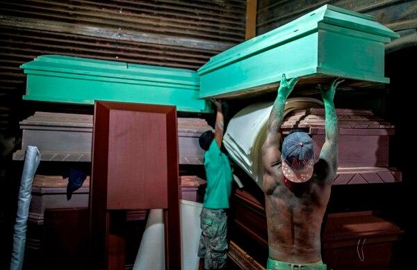 La funeraria La Amistad en Managua, trabaja duro haciendo ataúdes ante la muerte que trae el coronavirus. Foto AFP.