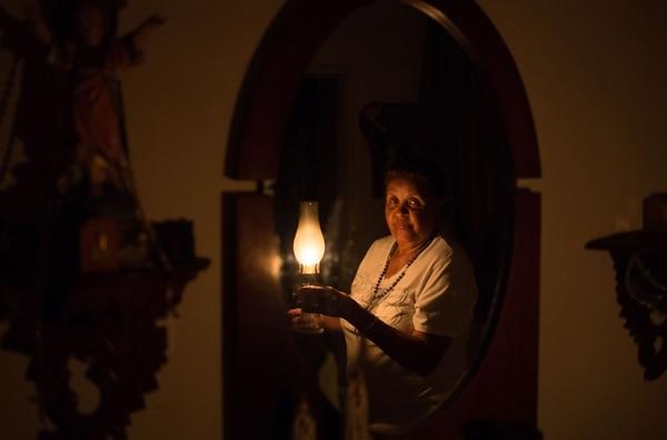 Doña Elvia es conserje en un edificio y se la tiene que jugar con velas. AFP