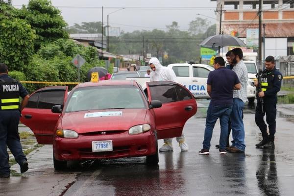 Los agentes revisaron el carro en busca de alguna pista sobre los sospechosos. Foto Reyner Montero.