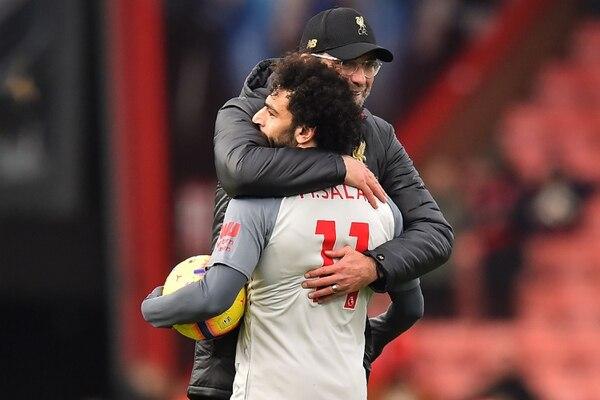 El técnico Jurgen Kloop felicita al delantero Mohamed Salah por sus tres goles de este sábado, que lo llevaron al primer lugar de los artilleros en la Premier Inglesa. AFP