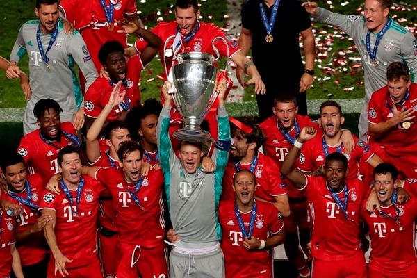 Bayern Munich's German goalkeeper Manuel Neuer (C) celebrates with teammates and the trophy after Bayern won the UEFA Champions League final football match between Paris Saint-Germain and Bayern Munich at the Luz stadium in Lisbon on August 23, 2020. (Photo by Manu Fernandez / POOL / AFP)