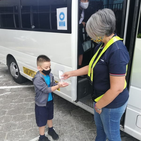 Shirley Miranda Núñez, quien transportará estudiantes en su micro, le da alcohol en gel a Josué Alfaro Sánchez, quien va al kinder. Foto Eduardo Vega