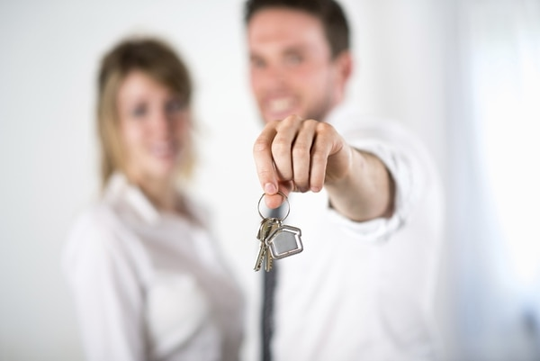 cheerful couple holding house keys