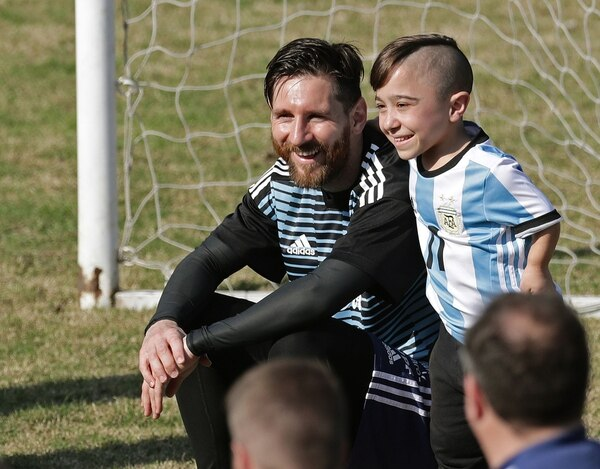Argentina's national football team forward Lionel Messi poses with a supporter during a training session at the Tomas Duco stadium in Buenos Aires on May 27, 2018 ahead of the FIFA World Cup. / AFP PHOTO / Alejandro PAGNI