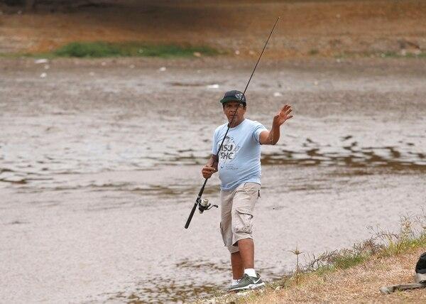 Ramón rescata a los peces que quedan en la orilla. Foto: Albert Marín.