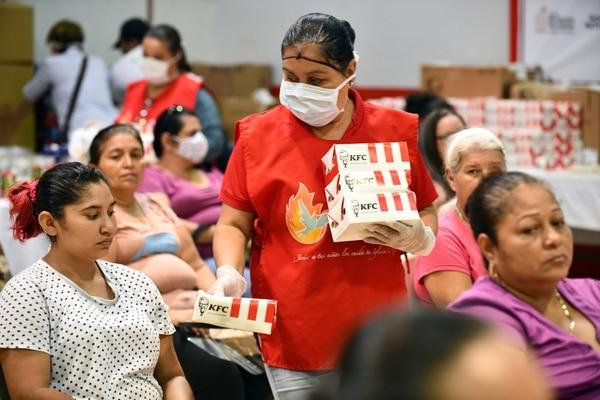 Mientras esperaban a ser llamados para darles el diario les dieronm pollito porque pancita llena, corazón contento. Foto Jorge Castillo.