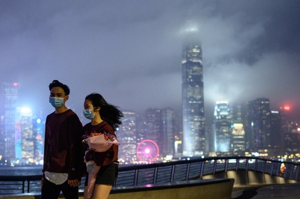 A couple wears face masks as a preventative measure against the COVID-19 coronavirus, as they walk along the promenade in Tsim Sha Tsui of Hong Kong on February 14, 2020. - The death toll from China's virus epidemic neared 1,400 on Friday with six medical workers among the victims, underscoring the country's struggle to contain a deepening health crisis. (Photo by Philip FONG / AFP)