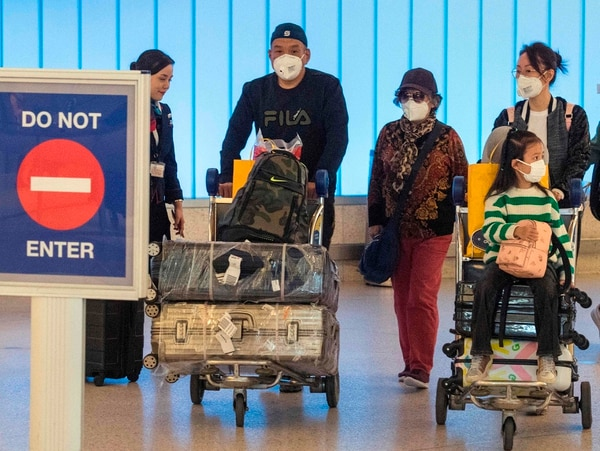 Passengers wear face masks to protect against the spread of the Coronavirus as they arrive on a flight from Asia at Los Angeles International Airport, California, on January 29, 2020. - A new virus that has killed more than one hundred people, infected thousands and has already reached the US could mutate and spread, China warned, as authorities urged people to steer clear of Wuhan, the city at the heart of the outbreak. (Photo by Mark RALSTON / AFP)