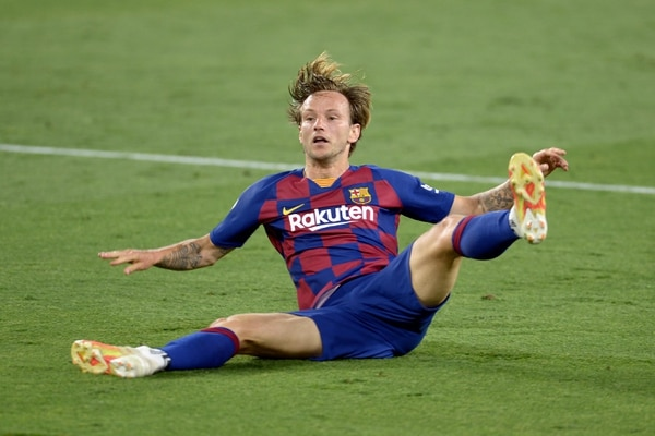 Barcelona's Croatian midfielder Ivan Rakitic falls during the Spanish league football match between Sevilla FC and FC Barcelona at the Ramon Sanchez Pizjuan stadium in Seville on June 19, 2020. (Photo by CRISTINA QUICLER / AFP)
