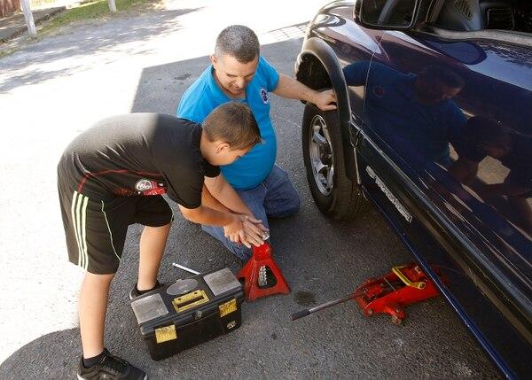 Su hijo Fabián le ayuda a pasar herramientas. Foto: Albert Marín.