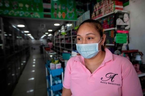 La empresa privada se esfuerza por cumplir disposiciones sanitarias sin ayuda de nadie, en la foto, una empleada de supermercado usa mascarilla por orden de su empresa y no del Gobierno. Foto AFP.