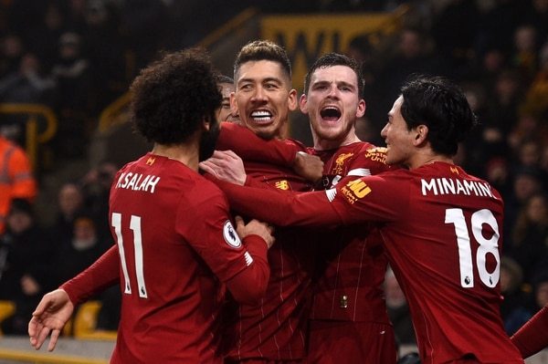 TOPSHOT - Liverpool's Brazilian midfielder Roberto Firmino (CL) celebrates with teammates after he scores the team's second goal during the English Premier League football match between Wolverhampton Wanderers and Liverpool at the Molineux stadium in Wolverhampton, central England on January 23, 2020. (Photo by Oli SCARFF / AFP) / RESTRICTED TO EDITORIAL USE. No use with unauthorized audio, video, data, fixture lists, club/league logos or 'live' services. Online in-match use limited to 120 images. An additional 40 images may be used in extra time. No video emulation. Social media in-match use limited to 120 images. An additional 40 images may be used in extra time. No use in betting publications, games or single club/league/player publications. /