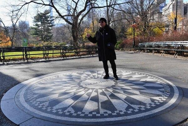 Susan Ryan, guía de turistas, posa en el punto del Parque Central, en Nueva York donde se recuerda a Lennon. AFP