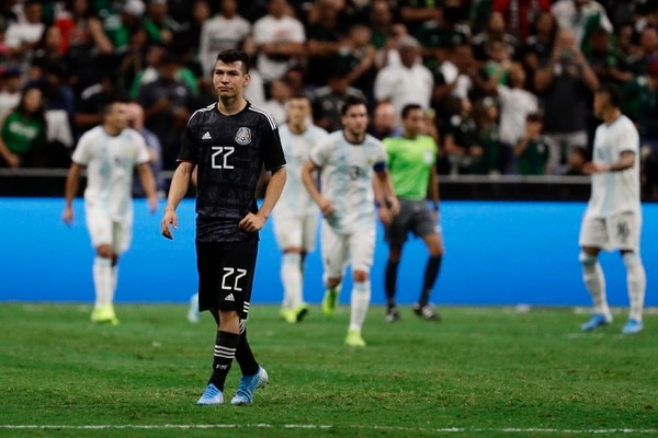 Mexico's Hirving Lozano (22) walks up field after Argentina's Leandro Paredes (5) scored on a penalty kick during the first half of an international friendly soccer match Tuesday, Sept. 10, 2019, in San Antonio. (AP Photo/Eric Gay)