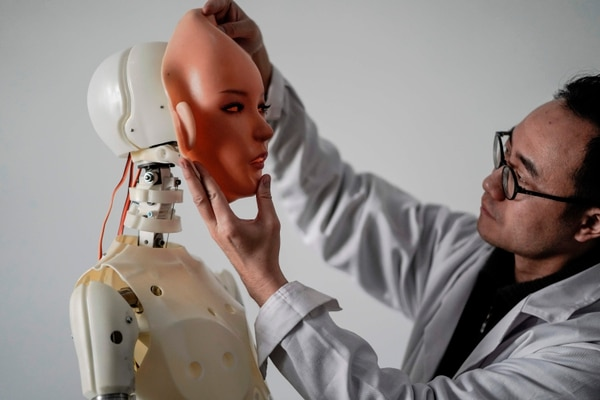 TOPSHOT - This photo taken on February 1, 2018 shows an engineer holding a silicon face against the head of a robot at a lab of a doll factory of EXDOLL, a firm based in the northeastern Chinese port city of Dalian. With China facing a massive gender gap and a greying population, a company wants to hook up lonely men and retirees with a new kind of companion: