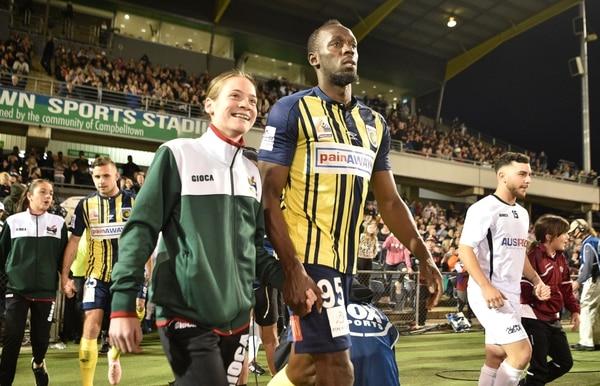 Esta joven dejó ver la alegría que le generó saltar al terreno de juego de la mano de Bolt. (Photo by PETER PARKS / AFP) /