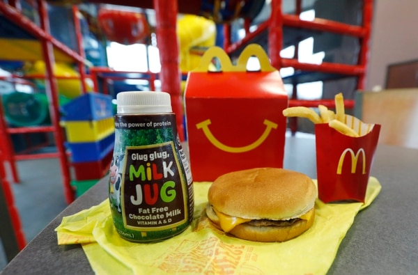 A Happy Meal featuring non-fat chocolate milk and a cheeseburger with fries, are arranged for a photo at a McDonald's restaurant in Brandon, Miss., Wednesday, Feb. 14, 2018. McDonald's will soon banish cheeseburgers and chocolate milk from its Happy Meal menu in an effort to cut down on the calories, sodium, saturated fat and sugar that kids consume at its restaurants. Diners can still ask specifically for cheeseburgers or chocolate milk with the kid's meal, but the fast-food company said that not listing them will reduce how often they're ordered. (AP Photo/Rogelio V. Solis)