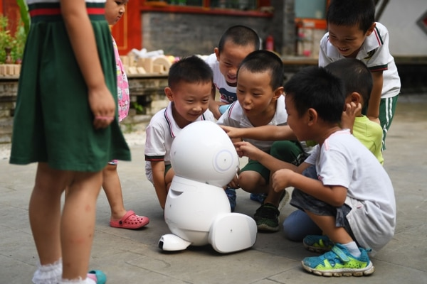 This photo taken on July 30, 2018 shows children playing with a Keeko robot after a class at the Yiswind Institute of Multicultural Education in Beijing. - In China, robots are being developed to deliver groceries, provide companionship to the elderly, dispense legal advice and now, as Keeko's creators hope, join the ranks of educators. (Photo by GREG BAKER / AFP) / TO GO WITH China-science-education-robot, FEATURE by Elizabeth LAW and Danni ZHU